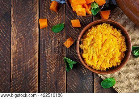 Delicious Homemade Pumpkin Porridge On Wooden Background. Healthy Vegan Food. Top View