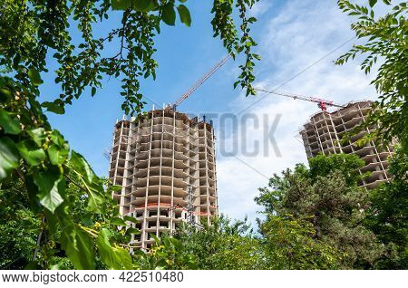 Building Construction Site At Sunny Day. Concrete Highrise Construction Site With Tower Crane Agains