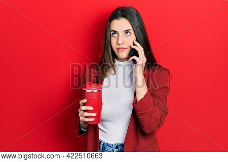Young brunette teenager talking on smartphone and drinking coffee smiling looking to the side and staring away thinking.