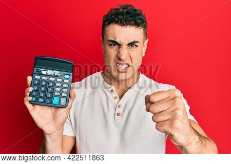Hispanic young man showing calculator device annoyed and frustrated shouting with anger, yelling crazy with anger and hand raised
