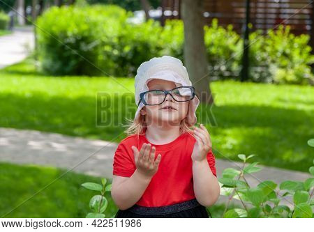 Outdoor Portrait Of A Cute Little 2, 5 Year Old Girl Wearing Eyeglasses. Funny And Pretty Girl In Th