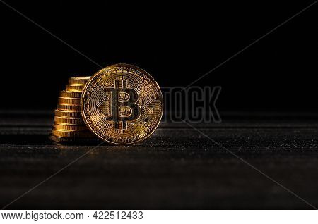 Leader In Cryptocurrency Bitcoin Btc On A Top Of Coins Against Black Wooden Surface. Closeup Golden