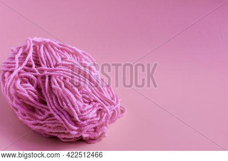 A Skein Of Pink Yarn On A Pink Background Close-up. Concepts Of Needlework And Self-isolation