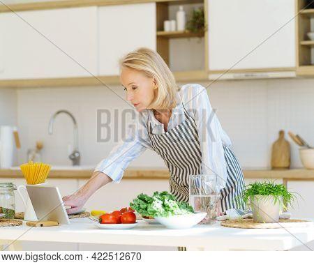 Focused Senior Woman In Apron Looking In Internet Video Recipe On Digital Tablet While Cooking In Ki