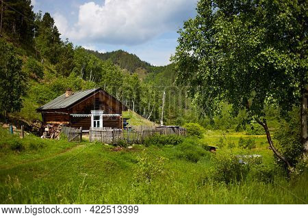 An Old Country House In The Middle Of A Forest And Mountains On A Warm Summer Day. Seclusion, Rural