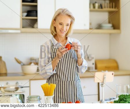 Happy 60s Woman Food Blogger In Kitchen Apron Recording Video Recipe On Phone For Followers In Socia