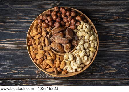 Natural Organic Raw Nuts Wooden Plate On Dark Background Top View. Platter Board With Healthy Snack: