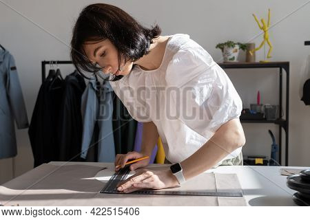 Tailoring Process: Girl Dressmaker Measuring Cloth Material For Sewing Clothes. Young Female Tailor