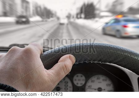 The Driver Hand On The Steering Wheel Inside The Car Against The Background Of The City Road, Traffi