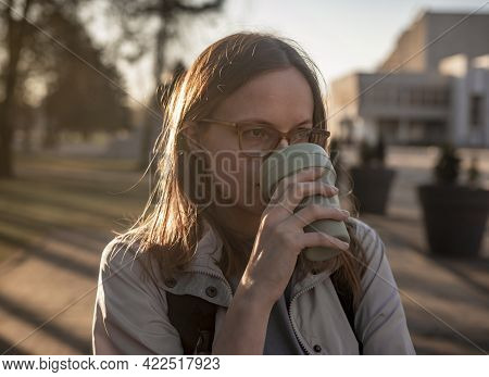 Young Real Candid Woman In Eyewear With Reusable Coffee Cup In Hands, Drinking Coffee From Eco Mug W