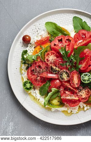 Salad With Red, Yellow, Green Tomatoes, Arugula And Ricotta Cheese.