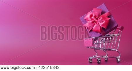 Shopping Trolley With Gift Box Isolated On Purple Background.