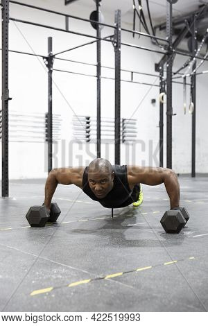 African American Man Doing Pushups With Kettlebells On Gym Floor. Intense Workout Of Body Strength.