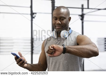 Portrait Of African American Male Sportsman Looking At His Wristwatch. Concept Of Technology In Spor