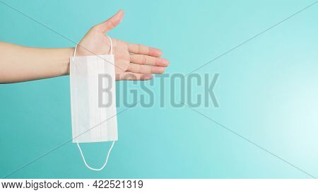 Hand Is Holding White Surgical Face Mask Or Disposable Mask On Mint Green Or Tiffany Blue Background