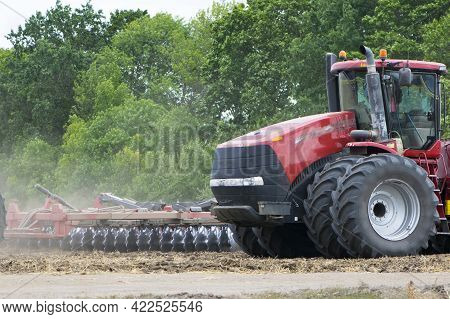 Red Tractor With A Plow On An Agricultural Field. Work In The Field With A Big Red Tractor Close-up,
