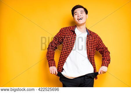 Cheerful Asian Guy In A Plaid Shirt Pulls Out Empty Pockets With His Hands And Looks To The Side
