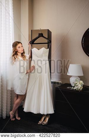 Bride In A White Silk Robe Near The Wedding Dress Hanging On A Hanger.