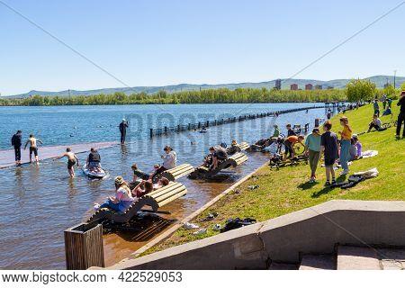 Krasnoyarsk, Russia - June 1, 2021: Careless People Rest On The Flooded City Embankment. Flooding Of