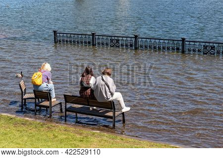 Krasnoyarsk, Russia - June 1, 2021: Girls Sit On Benches On A Flooded City Embankment. Flooding Of Y