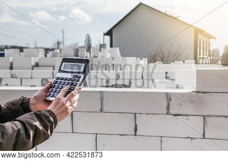 Calculation Of Building Materials. Woman Calculates Cost Of Building House. Calculator On Background