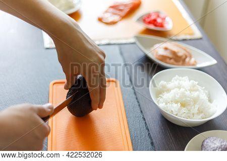 Young Boy Cutting Avocado Preparing Sushi At Home