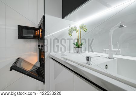 Luxury large modern white and black kitchen interior used as showcase, microwave and electric oven doors are open