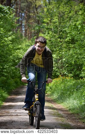A Teenager About 14 Years Old Wearing Glasses Is Quickly Riding A Children's Bike Along A Forest Pat