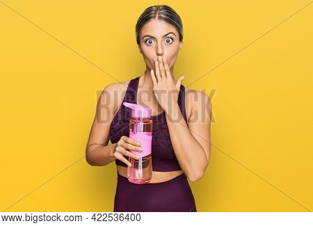 Beautiful blonde woman wearing sportswear holding water bottle covering mouth with hand, shocked and afraid for mistake. surprised expression