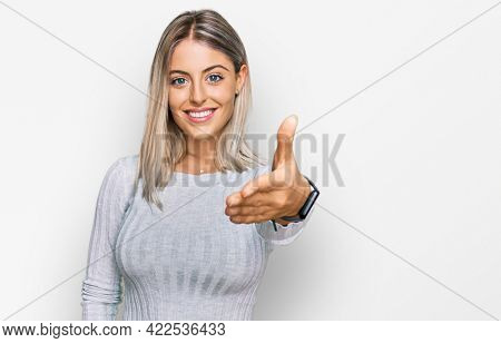 Beautiful blonde woman wearing casual clothes smiling friendly offering handshake as greeting and welcoming. successful business.
