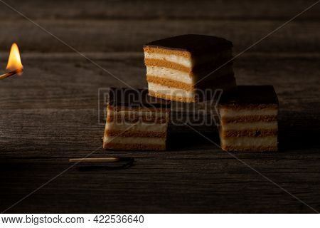 Three Slices Of Gerbeaud Cake, Lit By The Fire Of A Burning Match, Are Lying On Weathered Wood Plank