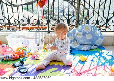 Small Child Sits On A Colored Rug On The Balcony Near A Plastic Box With Colorful Toys And Unscrews