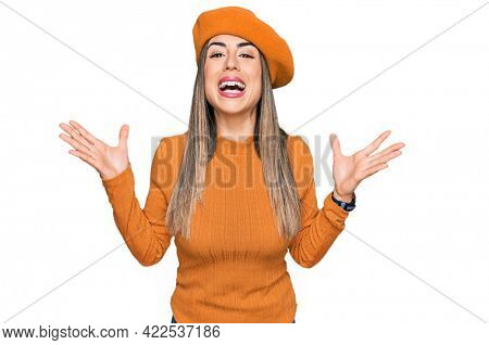 Young hispanic woman wearing french look with beret celebrating mad and crazy for success with arms raised and closed eyes screaming excited. winner concept