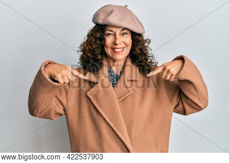 Middle age hispanic woman wearing french look with beret looking confident with smile on face, pointing oneself with fingers proud and happy.