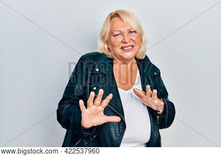 Middle age blonde woman wearing leather jacket disgusted expression, displeased and fearful doing disgust face because aversion reaction. with hands raised
