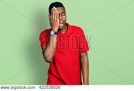 Young african american man wearing casual red t shirt yawning tired covering half face, eye and mouth with hand. face hurts in pain.