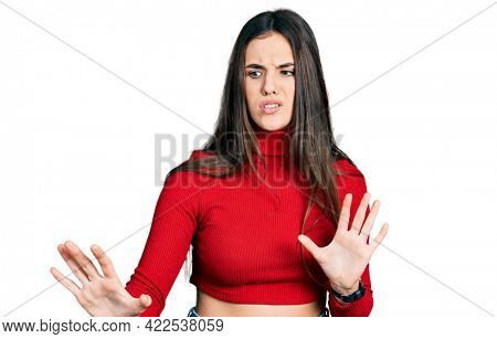 Young brunette teenager wearing red turtleneck sweater disgusted expression, displeased and fearful doing disgust face because aversion reaction.
