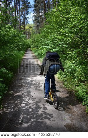 A Teenager About 14 Years Old Funny Rides A Child's Bike Along A Forest Path With A Backpack. Rear P
