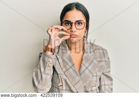 Young brunette woman wearing business jacket and glasses mouth and lips shut as zip with fingers. secret and silent, taboo talking