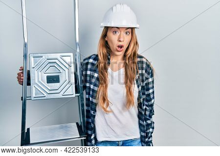 Young caucasian woman wearing hardhat holding ladder scared and amazed with open mouth for surprise, disbelief face