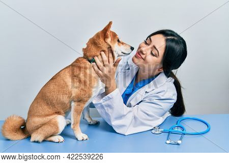Veterinarian woman wearing uniform at the clinic, hugging dog with love