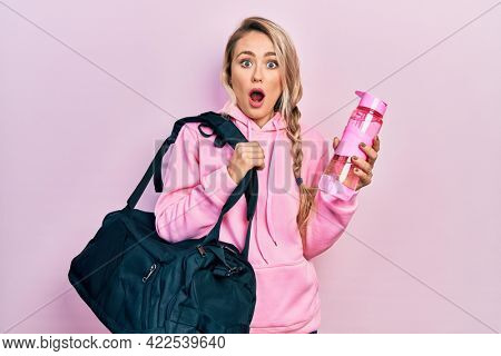 Beautiful young blonde woman holding gym bag and water bottle in shock face, looking skeptical and sarcastic, surprised with open mouth