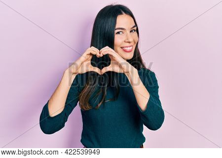 Young brunette woman wearing casual winter sweater smiling in love doing heart symbol shape with hands. romantic concept.