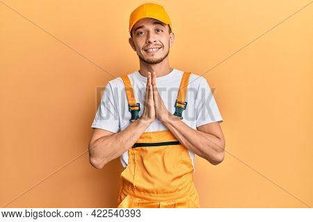 Hispanic young man wearing handyman uniform praying with hands together asking for forgiveness smiling confident.