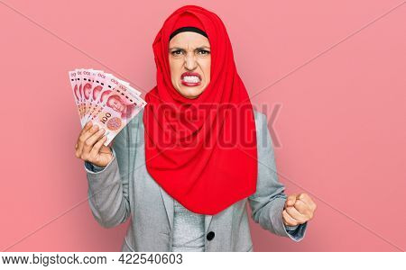 Beautiful hispanic woman wearing islamic hijab holding chinese yuan banknotes annoyed and frustrated shouting with anger, yelling crazy with anger and hand raised