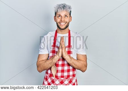 Young hispanic man with modern dyed hair wearing apron begging and praying with hands together with hope expression on face very emotional and worried. begging.