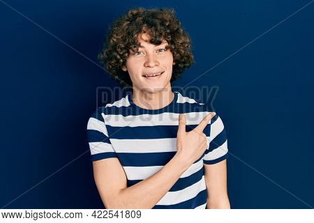 Handsome young man wearing casual striped t shirt cheerful with a smile of face pointing with hand and finger up to the side with happy and natural expression on face