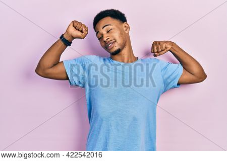 Young african american man wearing casual blue t shirt stretching back, tired and relaxed, sleepy and yawning for early morning