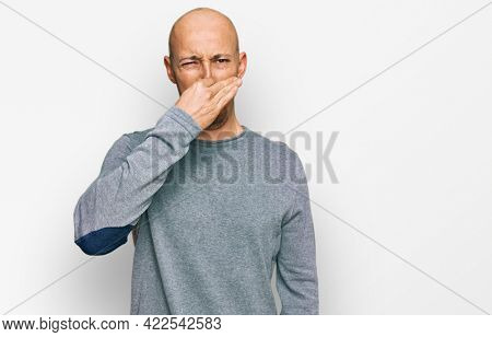 Bald man with beard wearing casual clothes smelling something stinky and disgusting, intolerable smell, holding breath with fingers on nose. bad smell