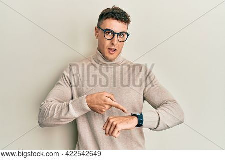 Hispanic young man wearing casual turtleneck sweater in hurry pointing to watch time, impatience, upset and angry for deadline delay